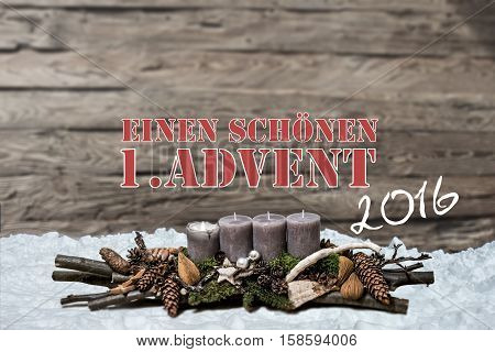 Merry Christmas decoration advent 2016 with burning grey candle Blurred background snow text message german 1st