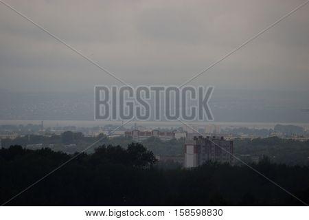 grey rainy foggy cityscape cloudy sky distant buildings