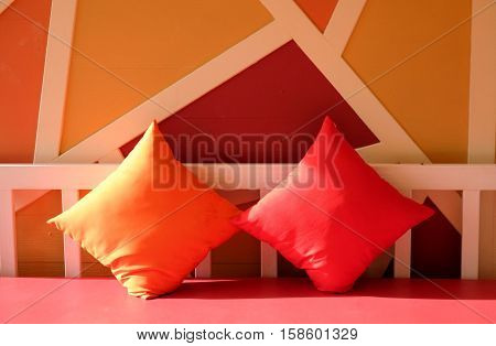 Colorful backrest pillow on the red sofa-bed.