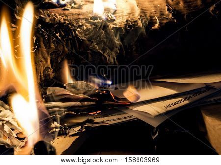 Holiday spending and Getting out of holiday christmas debt image with copy space conceptual finance and spending habits. Burning credit card bills and collection letters in holiday fireplace with flames in pile of bills and statements with words card