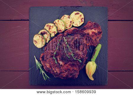 Rib-eye steak on black slate plate over wooden planks, toned image