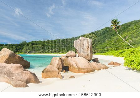 Beautifully shaped granite boulders in the turquoise sea and a perfect white sand at Anse Coco, La Digue island, Seychelles