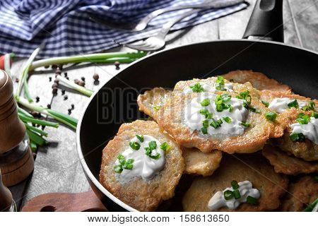 Frying pan with tasty potato pancakes for Hanukkah on wooden table, closeup