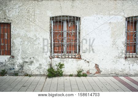 Three windows closed with brick and cement