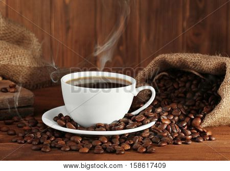 Cup of fresh coffee and sack with beans, closeup