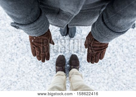 Male and Female boots standing on asphalt covered gritty snow surface. Rough snowy surface. Textplace. Cold Winter. Top view