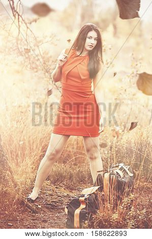 Fashionable young Asian woman in the red dress and carrying case in the autumn on a short trip.