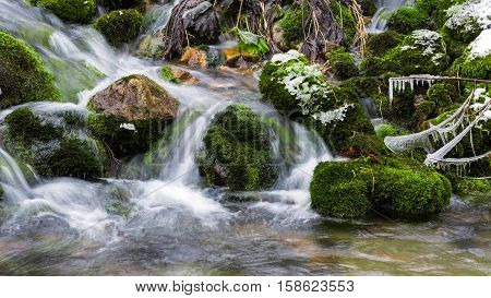 Stones covered with moss in mountain stream long exposure