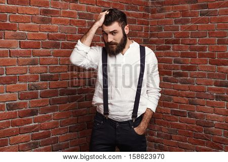 Young handsome man in suit with suspenders correcting hairstyle over brick background. Copy space.