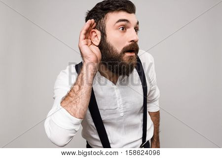 Young handsome brunet man in suit with suspenders eavesdroping over white background. Copy space.