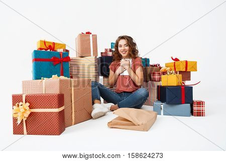 Young beautiful curly girl sitting on floor among gift boxes with just opened present tablet Isolated Copy space