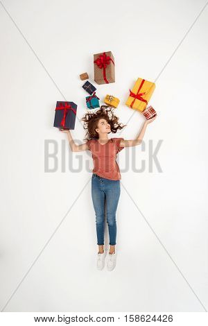 Young beautiful curly girl lying among gift boxes Shot from above Isolated Copy space