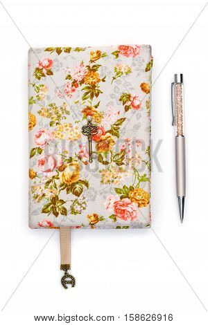 Beautiful handmade paper notebook in hard floral cover. Bokmark ribbon with horseshoe pendant detail. Scrapbooking. Pen lying aside. Isolated on white. Copy space.