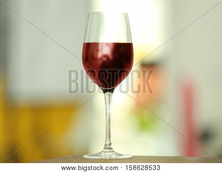 Glass with red wine on table