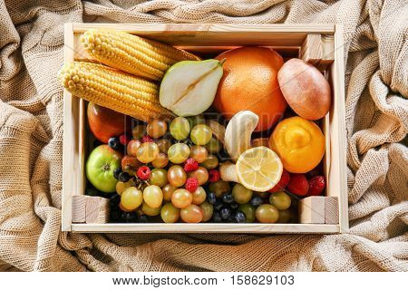Assortment of fruits and vegetables in wooden crate, top view