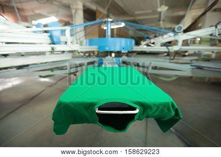 Green t-shirt silk screen printing machine, look of the mock up tshirt before printing process, horizontal image