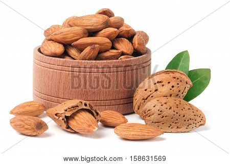Almonds in a wooden bowl with leaves isolated on white background.