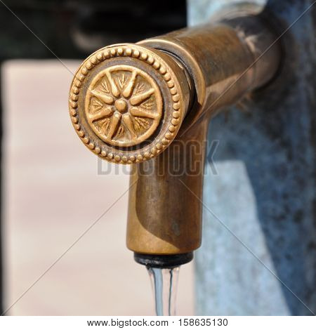 water tap made of brass with flowing water
