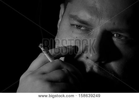 Young man smoking cigarette black and white