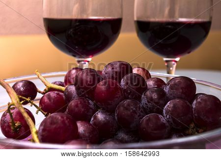 wine in the wine glass grape in the vase on the table
