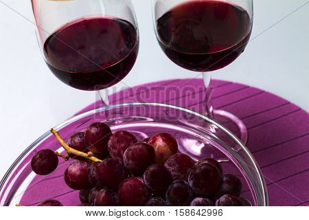 red wine in the wine glass grape in the vase on the glass table