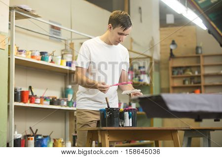 Young male worker choosing printing surface and appropriate inks for screen printing worker man mixing colors for screen printing on clothing fabric technique