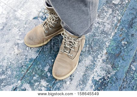 Female legs wearing warm winter boots standing on a wooden plank painted blue overhead shot