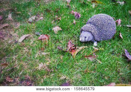 A decorative hedgehog on the autumn grass.