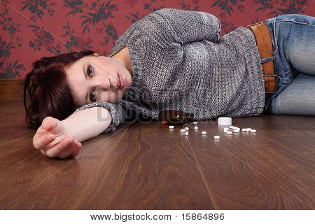 Overdose de adolescente em pílulas, deitado no chão
