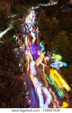 ATLANTA, GA - SEPTEMBER 2016:  Colorful bright lanterns motion blur and streak as hundreds of people walk at night along the Beltline in the annual Atlanta Lantern Parade in the Old Fourth Ward in Atlanta GA on September 10 2016.