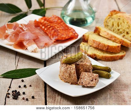Pork liver paste pâté with pickles and tapas on wooden background