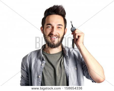 Portrait of young man holding car key, on grey background