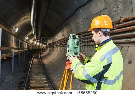 Surveyor with theodolite level at underground railway tunnel construction work