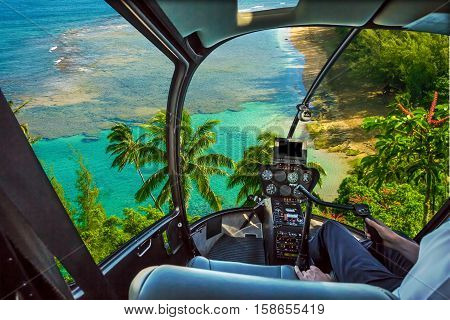 Helicopter cockpit flies in Kee Beach, Kauai, Hawaii, United States, with pilot arm and control board inside the cabin.