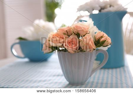 Rose bouquet in cup on blue napkin