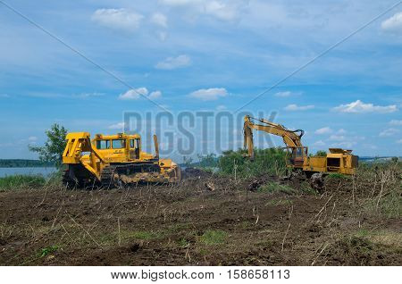 Eradicating forest with a bulldozer and digger. Excavator and bulldozer clearing forest land.
