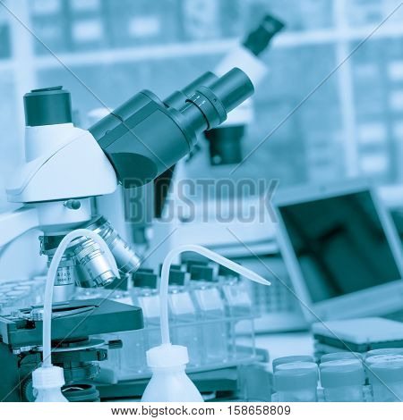 Science laboratory with a microscope, biological material samples and a computer on a desk. Selective focus with bokeh. Rack with samples and chemicals on the background. Blue toned image
