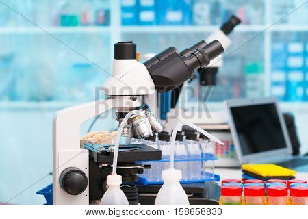 Science laboratory with a microscope, biological material samples and a computer on a desk. Selective focus with bokeh. Rack with samples and chemicals on the background