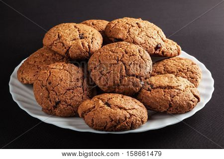 White plate of freshly baked oatmeal cookies with chocolate