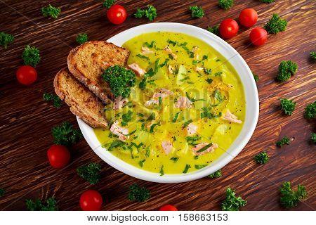 Creamy fish Salmon, leek, potato soup on wooden background.