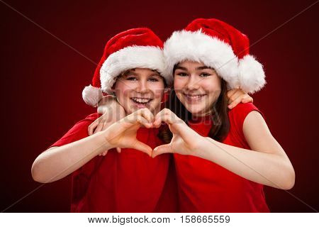 Christmas time - girl and boy with Santa Claus Hat showing heart shape