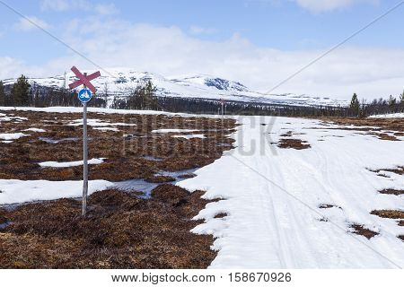 Snowmobile sign, red cross and trail in springtime. Snow, tussock and water in the mountains.