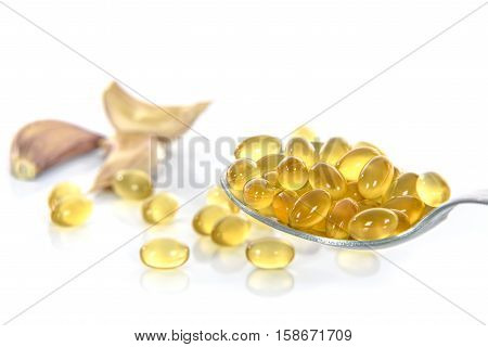 Garlic oil capsules with garlic cloves isolated on white background