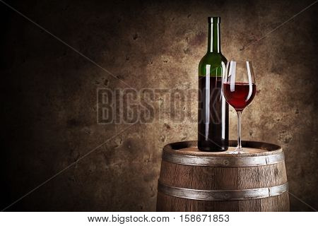 Bottle and glass of red wine on wooden barrel shot with dark background