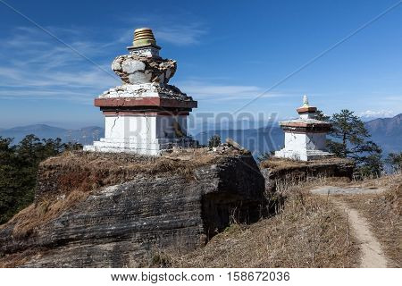 Buddhist Stupas In Remote Village In Himalayas With High Rocky Mountains On The Background. Two Budd