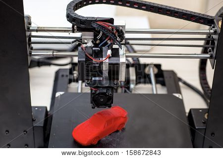 printer and printed models red machine is on the table