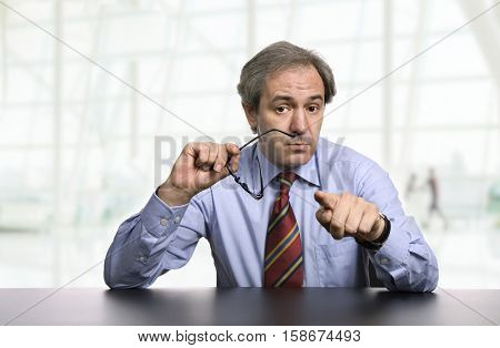mature business man on a desk pointing, at the office