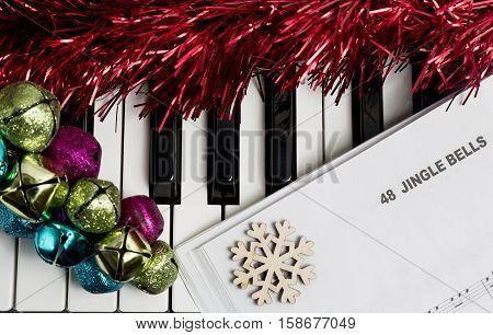 Christmas music concept. Printed music on the piano with jingle bells snowflake and spangle.