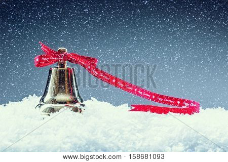 Christmas. Christmas Time. Christmas bell with red ribbon and snowy background. Happy christmas text.