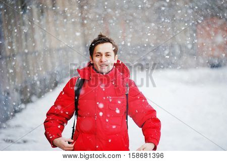 young handsome man in winter clothes enjoys the snow, cold, snowfall, blizzard